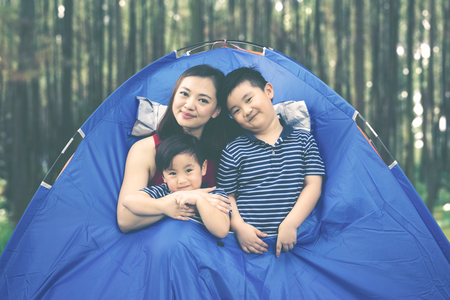 Image of beautiful woman smiling at the camera while embracing her sons in the tent Banque d'images