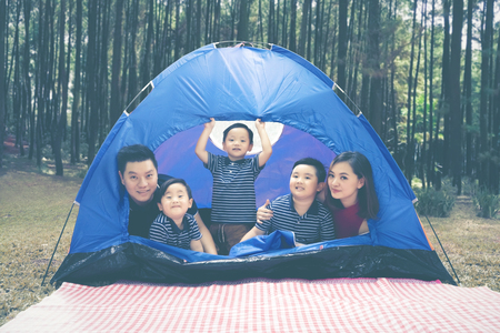 Picture of Asian family enjoying their holiday in the tent while camping in the forest Banque d'images