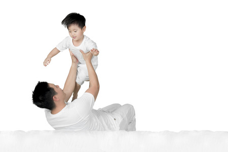 Image of young man lifting his son while lying on the bed, isolated on white background Banque d'images