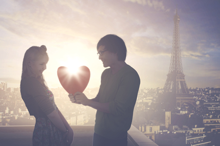 Image of young man giving a gift shaped heart to his girlfriend while standing on the rooftop with Eiffel tower background Banque d'images