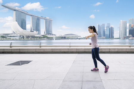 SINGAPORE, January 02, 2018: young woman looking at her wristwatch while running on the esplanade bridge