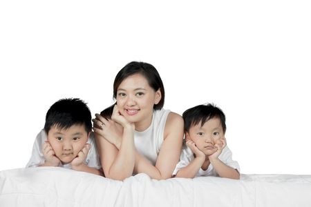 Beautiful woman smiling at the camera while lying with her two sons on the bed, isolated on white background