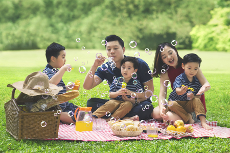 Picture of Asian family is blowing bubble soap while enjoying their holiday and picnicking in the park