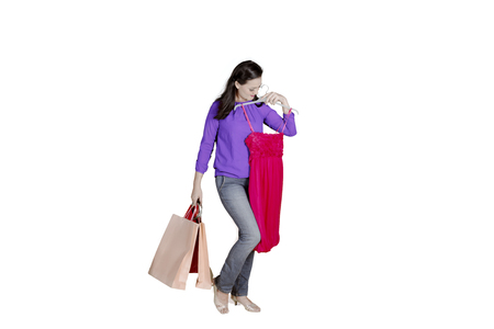 Picture of beautiful woman carrying shopping bags while trying new dress, isolated on white background
