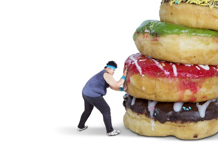 Diet concept. Fat man wearing sportswear while pushing donuts, isolated on white background