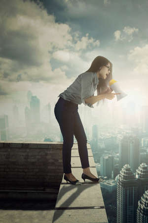 Portrait of angry businesswoman yelling by using a megaphone while standing on the building rooftop