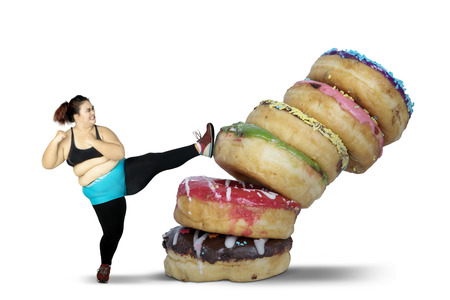 Diet Concept. Obese woman kicking stack of donuts while wearing sportswear. Isolated on white background