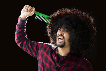 Picture of a young African man looks unhappy while trying to comb his frizzy hair