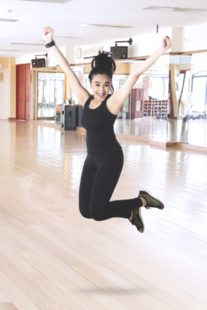 Beautiful woman looks excited while wearing black sportswear and jumping in the fitness center Stock Photo
