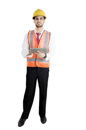 Full length of young foreman smiling at the camera while holding a digital tablet, isolated on white background Stock Photo
