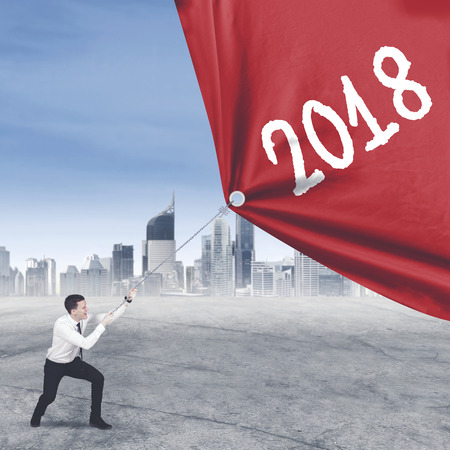 American businessman struggling to pull a fabric with numbers 2018 while standing near modern city background