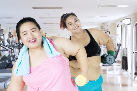 Two obese women smiling at the camera while doing a workout with dumbbell in the fitness center