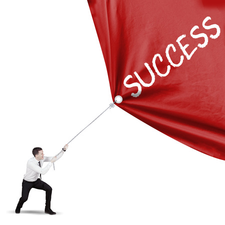American businessman using a chain to pull a banner with success word, isolated white background Stock Photo