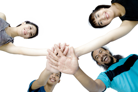 Low angle view of four young people joining their hands before doing a workout, isolated on white background