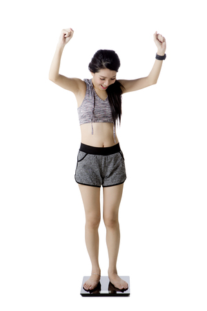Pretty girl expressing her success to loss weight while standing on the weighing scale