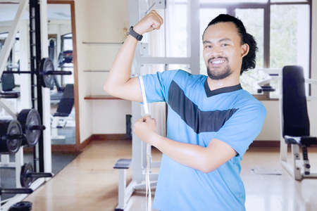 African man measuring his bicep by using a measure tape while standing in the fitness center Stock Photo