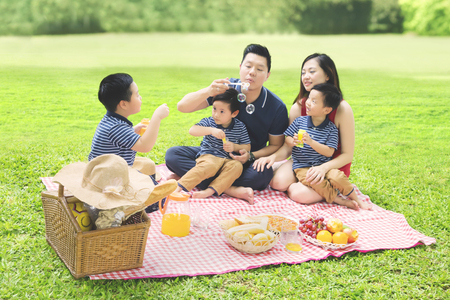 Picture of Chinese family playing with bubble soap while enjoying their holiday and picnicking in the park