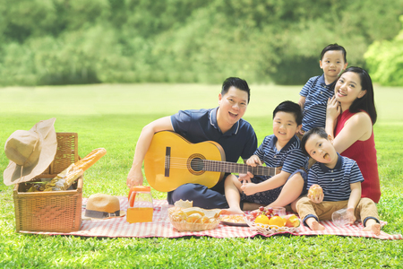 Picture of Chinese family enjoying their holiday and picnicking in the park while playing a guitar together