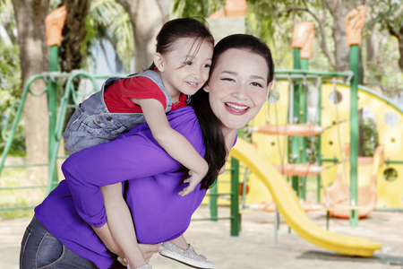 Picture of Caucasian woman looks happy while giving a piggyback ride her daughter in the playground Foto de archivo