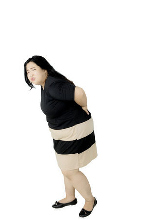 Portrait of obese woman having backache while standing in the studio, isolated on white background