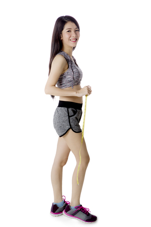 Full length of happy woman wearing sportswear while holding a measuring tape, isolated on white background