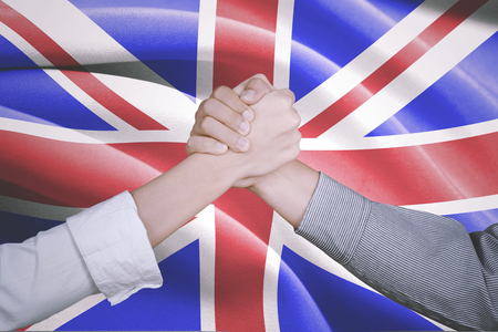 Symbolizing of peace. Two hands of business people posing partnership with England flag in the background Stock Photo