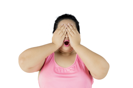 Picture of obese woman looks sad while closing her face with her hands, isolated on white background Stock Photo