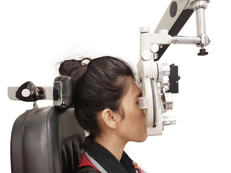 Picture of young woman examining her eyes with phoropter, isolated on white background
