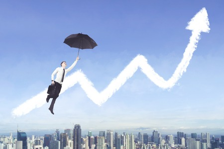 Picture of American businessman using an umbrella to flying with clouds shaped a growth chart Stock Photo