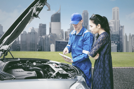 Picture of young male mechanic using a tablet to checking broken car while talking with his client in the roadside Stock Photo