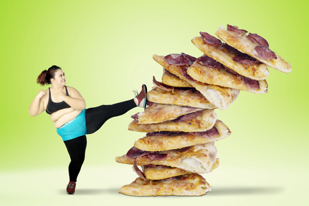 Diet concept. Overweight woman avoids to eat junk foods by kicking pizza. Shot with green screen background