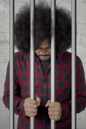 Portrait of an African male prisoner standing behind bars in the jail with regret expression Foto de archivo