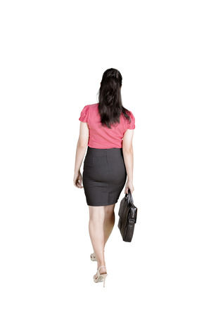 Back view of female manager holding a suitcase while walking in the studio, isolated on white background