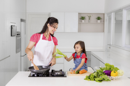 Image of little girl holding a mustard greens while helping her mother prepare meals in the kitchen