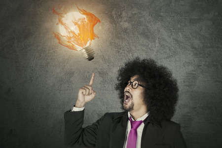 Creative concept of excited businessman with light bulb on fire