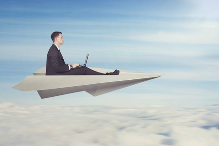 Businessman with laptop flying on a paper plane Stockfoto