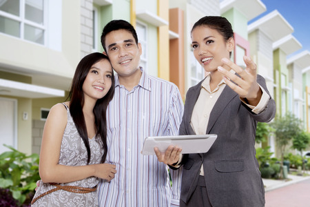 Real estate broker showing a new house for sell to a young Asian couple