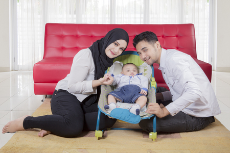 Happy family of father, mother, and baby boy posing in front of sofa Stock Photo