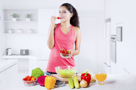 Indian woman tasting strawberry while preparing salad in a luxury kitchen