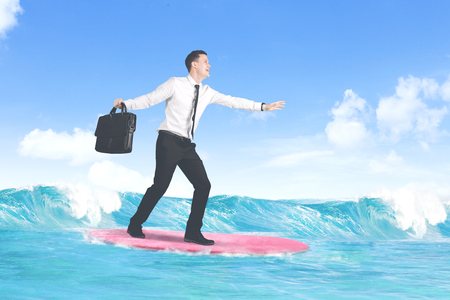 Carefree businessman enjoying freedom surfing at sea