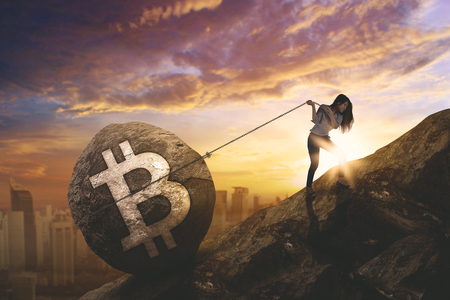 Young businesswoman using a chain to pull a stone with bitcoin symbol while climbing on the cliff