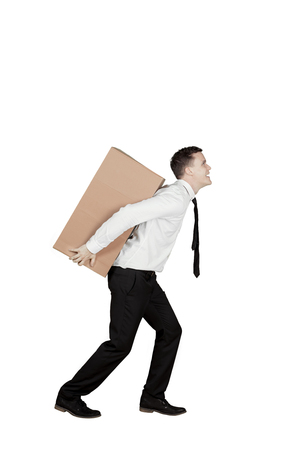 Portrait of American businessman carrying a box on his back, isolated on white background