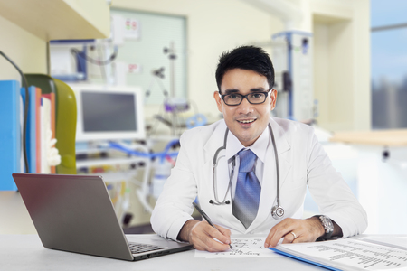 Portrait of friendly doctor writing an advice while smiling at camera in hospital Stock Photo