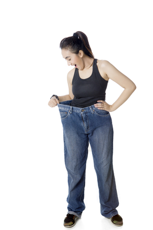 Arabian woman looks shocked while trying her old jeans and standing in the studio, isolated on white background