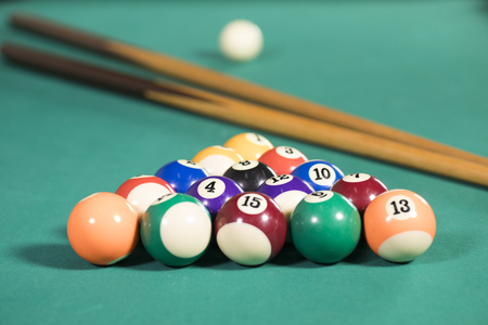 Picture of billiard balls and two sticks on the green pool table