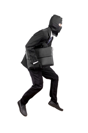 Thief dressed in black and wearing a balaclava stealing a bag isolated over white background Stock Photo