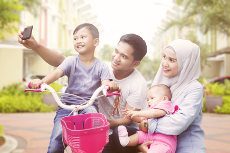 Happy muslim family taking selfie spending quality time in summer