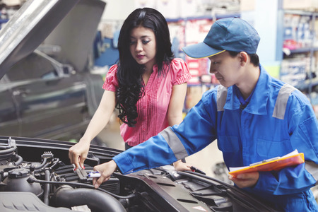 Car mechanic helping a customer fixing the car while holding a checklist Stock Photo
