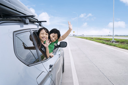 Happy siblings waving hands travel by car against blue sky. Summer road trip concept