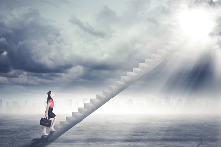 Businesswoman walking up staircase to door in sky with bright light shining down